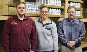 Three people standing in front of warehouse shelves of their product