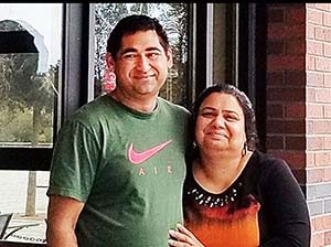Kummar and Puja Sharma standing outside their restaurant, Taste of India, in Mount Vernon, Wash.
